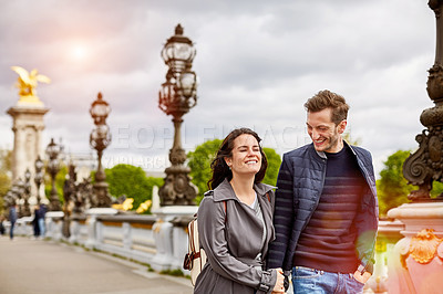 Buy stock photo Shot of a smiling young man standing on a bridge over the Seine River in Paris