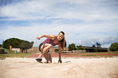 Buy stock photo Shot of a young woman landing in sand after a long jump