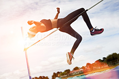 Buy stock photo Shot of a young woman in mid air doing a high jump on a sports field
