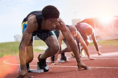 Buy stock photo Shot of a group of runners crouching in starting blocks before a race on a running track