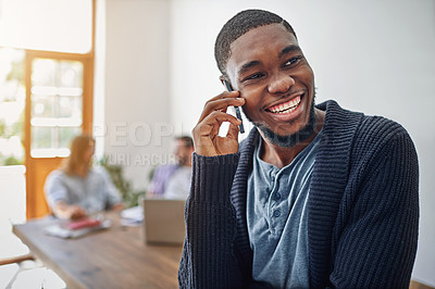 Buy stock photo Shot of a smiling young man talking on his cellphone in an office with colleagues in the background