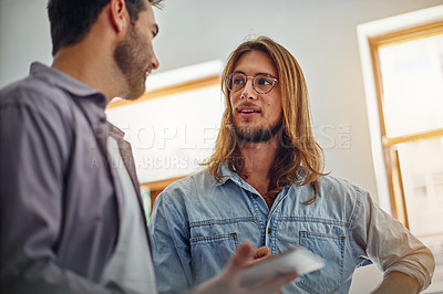Buy stock photo Shot of two colleagues talking together while standing in an office