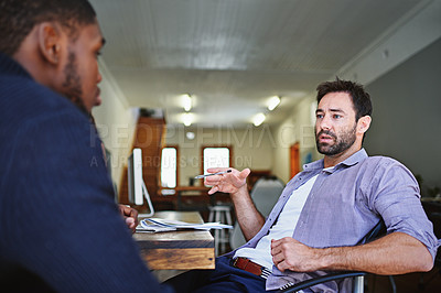 Buy stock photo Shot of two colleagues in deep discussion together while sitting at a desk in an office