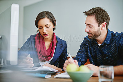 Buy stock photo Shot of two colleagues comparing paperwork while sitting at a desk in an office