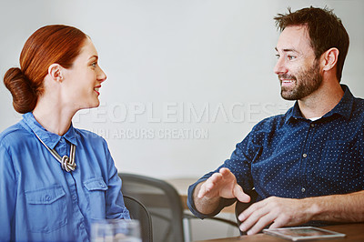 Buy stock photo Shot of two smiling colleagues talking together in an office
