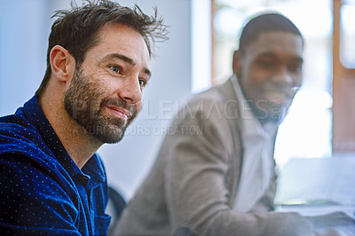 Buy stock photo Shot of two colleagues sitting together while working in an office