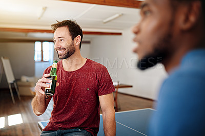 Buy stock photo Shot of colleagues talking and drinking beers together while winding down after work