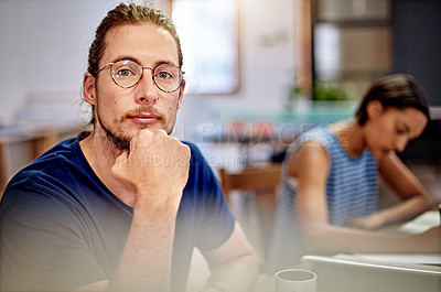 Buy stock photo Portrait of a focused young designer sitting in an office with a colleauge in the background