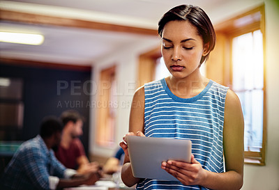 Buy stock photo Shot of a young woman standing in an office using a digital tablet with colleagues in the background