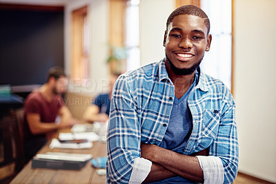 Buy stock photo Portrait of a smiling young man standing in an office with colleagues in the background