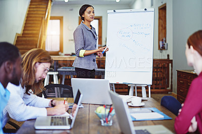 Buy stock photo Shot of a young woman giving a whiteboard presentation to colleagues in an office