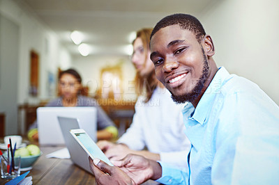 Buy stock photo Portrait of a young man sitting in an office using a digital tablet with colleagues in the background