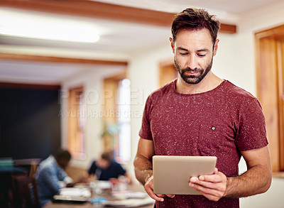 Buy stock photo Shot of a man standing in an office using a digital tablet with colleagues in the background