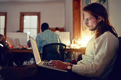 Buy stock photo Shot of a young designer working on a laptop in an office late in the evening