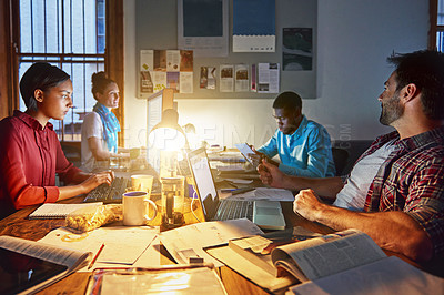 Buy stock photo Shot of a group of designers at work around a table in the evening