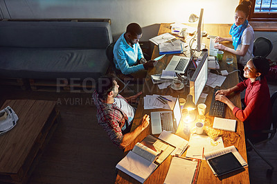 Buy stock photo High angle shot of a group of designers at work around a table in an office in the evening