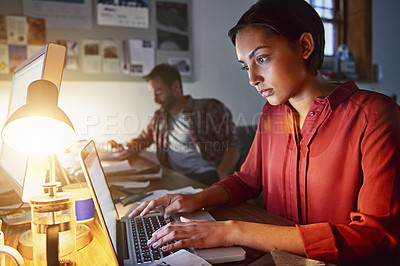 Buy stock photo Shot of a young woman working on a laptop in an office in the evening