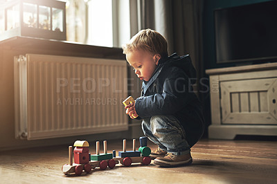 Buy stock photo Shot of an adorable little boy playing with his toy train at home