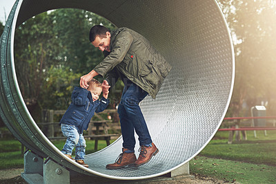 Buy stock photo Shot of a father and his little son playing together on a running wheel at the park
