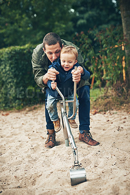 Buy stock photo Shot of a father and his little son playing together at the park
