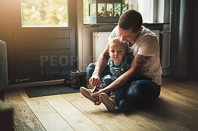 Buy stock photo Shot of a father helping his son put on his shoes at home