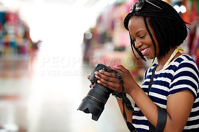 Buy stock photo A young female tourist looking through her photographs while standing in a grocery store