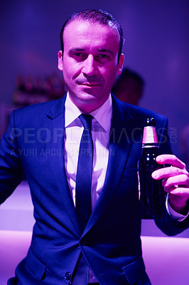 Buy stock photo Portrait of a businessan drinking a beer while sitting in a seedy Thai nightclub