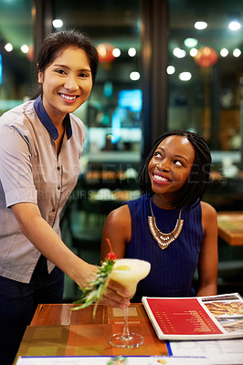 Buy stock photo Portrait of a young waitress serving a drink to her female customer