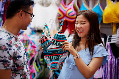 Buy stock photo Shot of a young woman asking her boyfriend's opinion on a bathing suit
