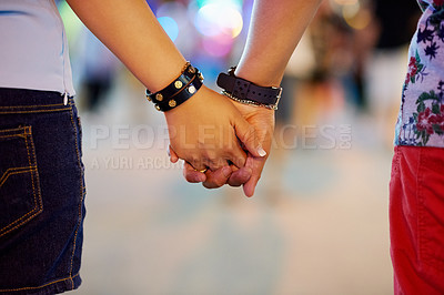 Buy stock photo Cropped shot of a couple holding hands while out in the city