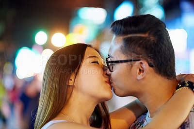 Buy stock photo Shot of a couple kissing while out in the city on a date