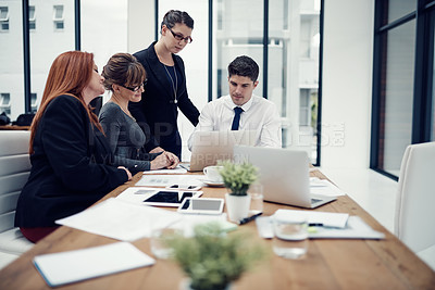 Buy stock photo Cropped shot of a group of businesspeople using a laptop together during a meeting in an office