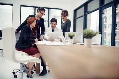 Buy stock photo Shot of group of businesspeople using a laptop together during a meeting in an office