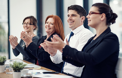 Buy stock photo Cropped shot of a group of businesspeople applauding while sitting in a boardroom