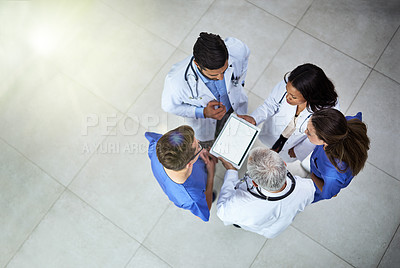Buy stock photo High angle shot of a diverse team of doctors using a digital tablet together