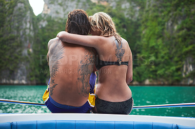 Buy stock photo Rear view shot of a young couple sitting on a boat at sea