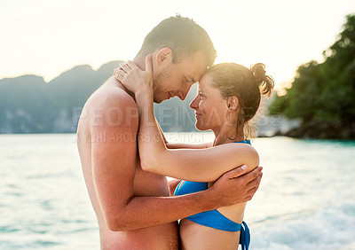 Buy stock photo Cropped shot of a young couple enjoying the day at the beach
