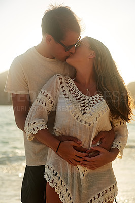 Buy stock photo Shot of an affectionate young couple on the beach at sunset