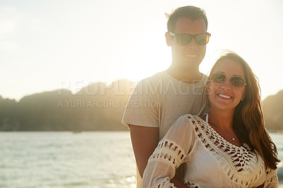 Buy stock photo Portrait of an affectionate young couple on the beach at sunset