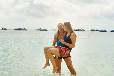Buy stock photo Shot of two young girlfriends enjoying a day at the beach on a summer's day
