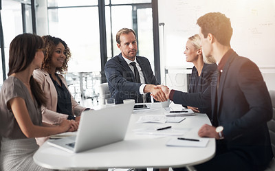 Buy stock photo Cropped shot of businesspeople shaking hands during a meeting in an office