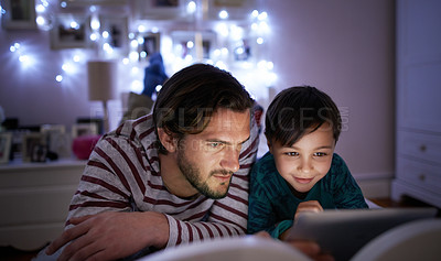 Buy stock photo Cropped shot of a young father reading a bedtime story to his son