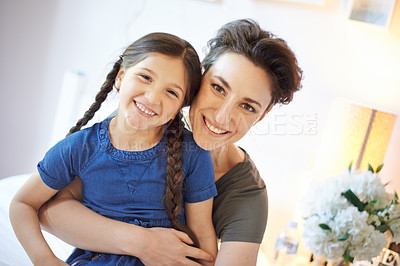 Buy stock photo Cropped portrait of a young mother and her daughter bonding at home