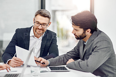 Buy stock photo Cropped shot of two businessmen going over some paperwork in their office