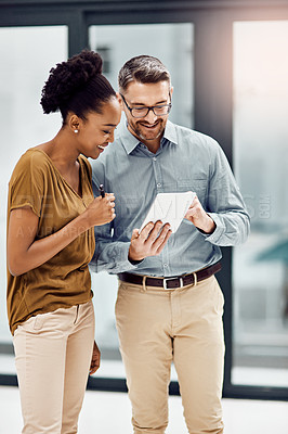 Buy stock photo Cropped shot of two businesspeople looking at a digital tablet in their office