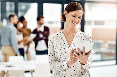 Buy stock photo Shot of a businesswoman using a tablet with her colleagues in the background