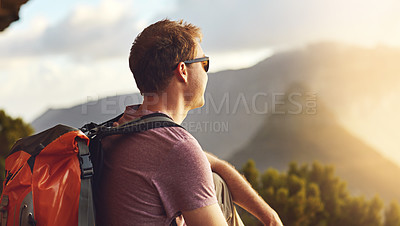 Buy stock photo Shot of a young man admiring the view from the top of a mountain