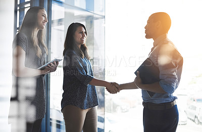 Buy stock photo Cropped shot of businesspeople shaking hands in an office