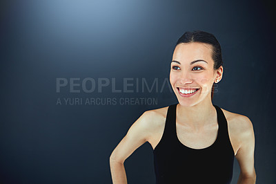 Buy stock photo Shot of a sporty young woman posing against a dark background