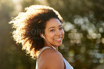 Buy stock photo Portrait of an attractive young woman listening to music while exercising outdoors